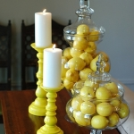 jars holding lemons next to yellow candles