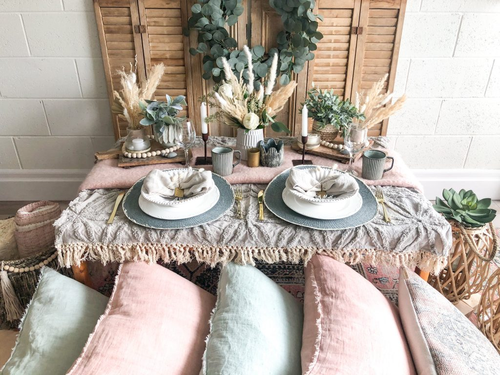 Bohemian-style table setting with linens, plates, flowers, pillows and other Boho items